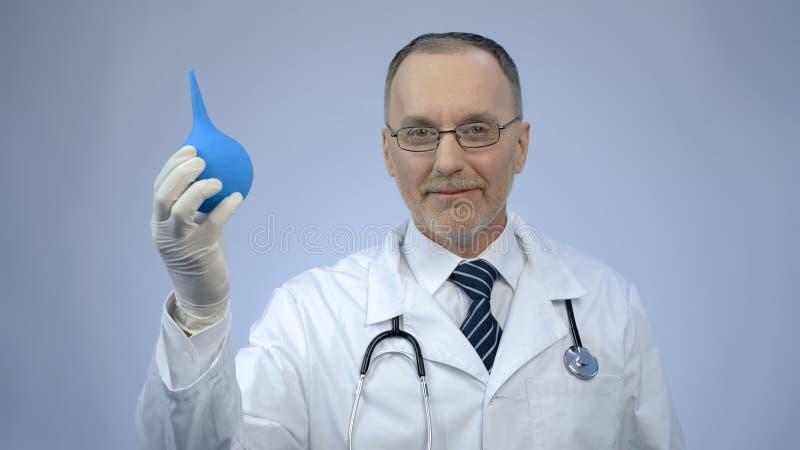 Docteur souri heureux de proctology montrant la seringue en caoutchouc et regardant l'appareil-photo image stock