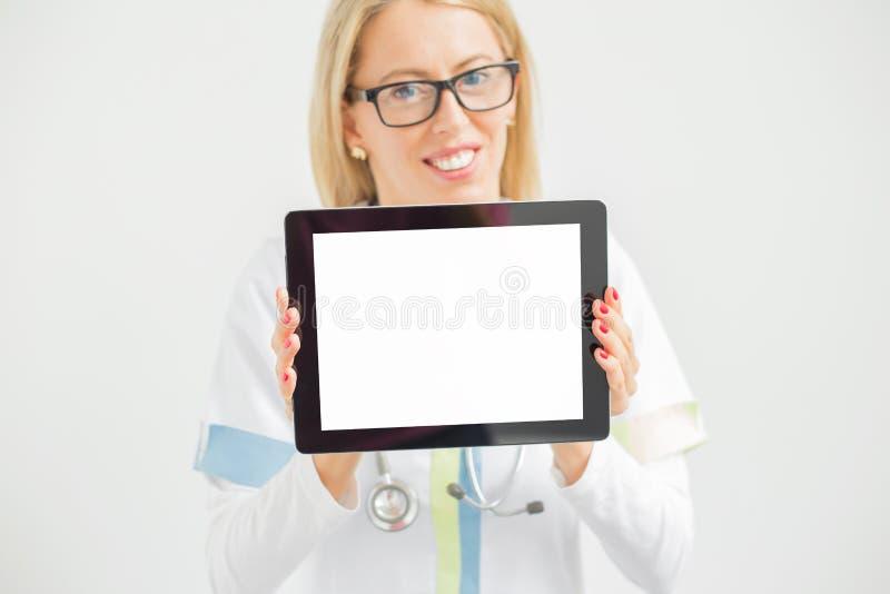 Docteur souriant et montrant le comprimé image stock