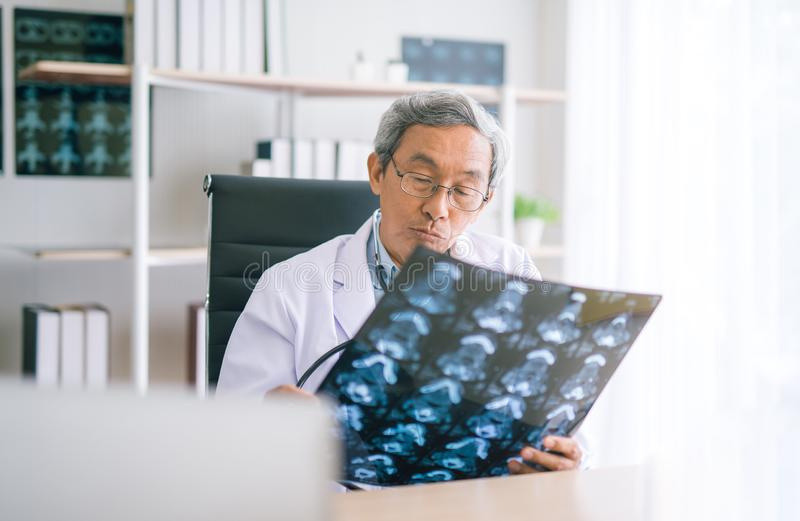 Docteur supérieur asiatique regardant le film de radiographie de la poitrine dans l'hôpital photos stock