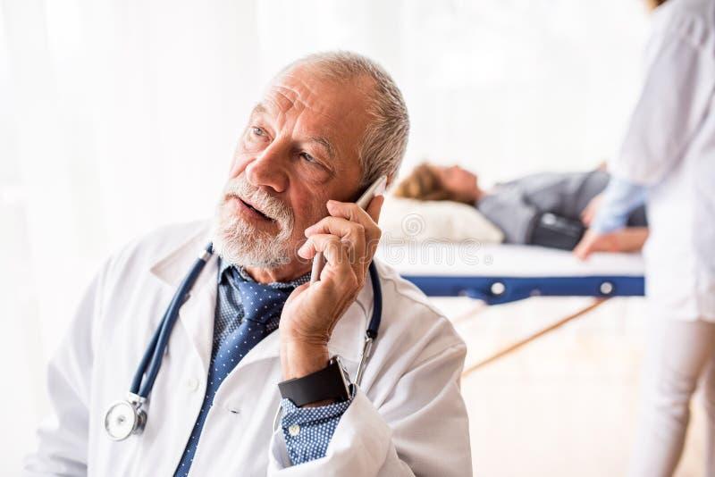 Docteur supérieur avec le smartphone dans son bureau photos stock