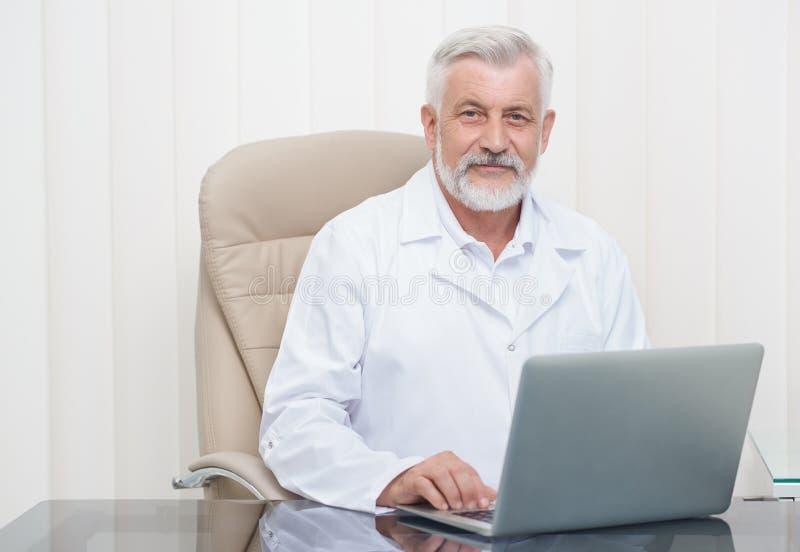 Docteur supérieur intelligent travaillant sur l'ordinateur portable dans le bureau images stock