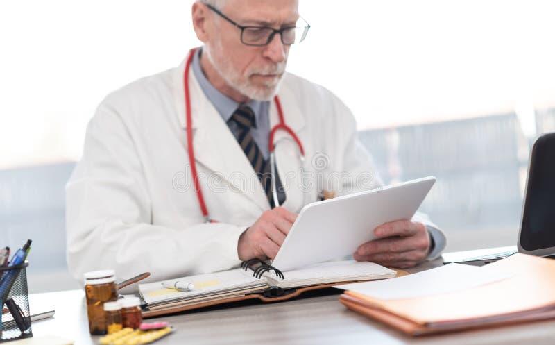 Docteur supérieur masculin utilisant le comprimé numérique photographie stock libre de droits