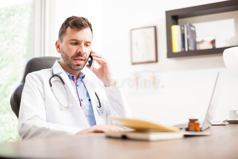 Docteur sur un appel téléphonique avec son patient photographie stock libre de droits