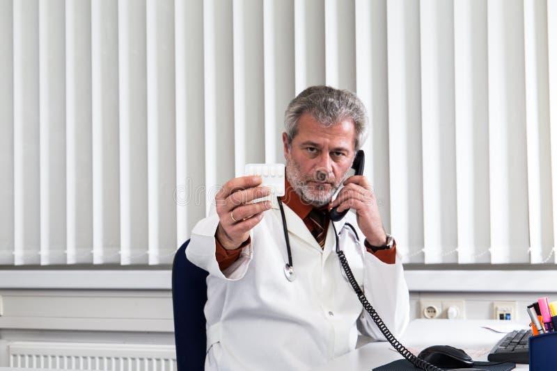 Docteur surchargé à son bureau photos libres de droits