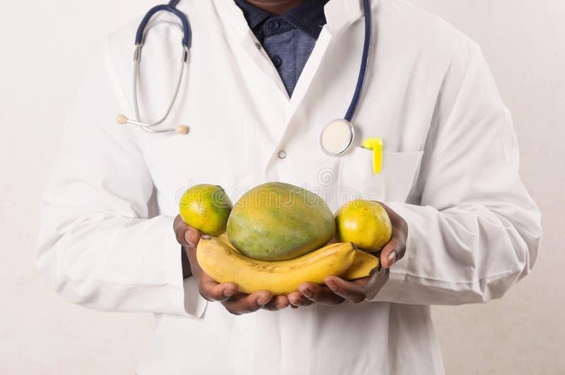 Docteur tenant et pr?sent des fruits dans des mains photos stock