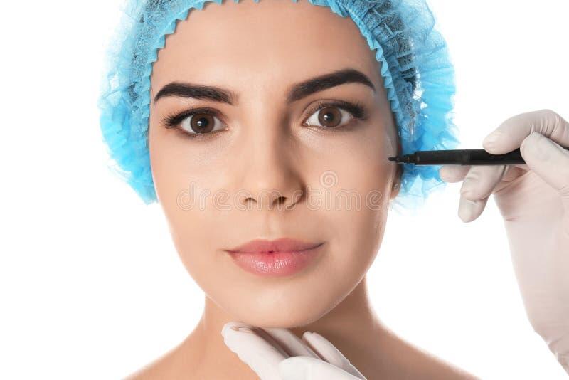 Docteur tenant le marqueur près du visage de la jeune femme d'isolement sur le blanc Concept de chirurgie plastique photos stock
