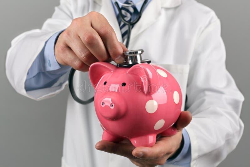 Docteur tenant le stéthoscope sur la tirelire photo stock