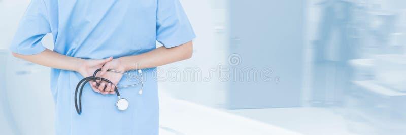 Docteur tenant un stéthoscope sur le fond bleu photo libre de droits