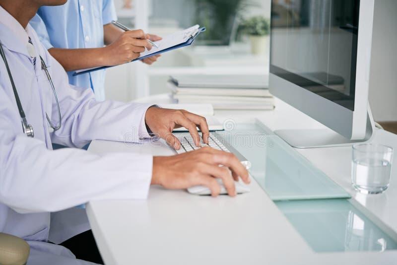 Docteur travaillant sur l'ordinateur photographie stock