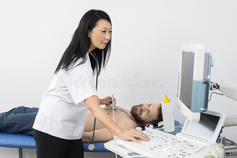 Docteur Using Ultrasound Machine tout en examinant le patient photo stock