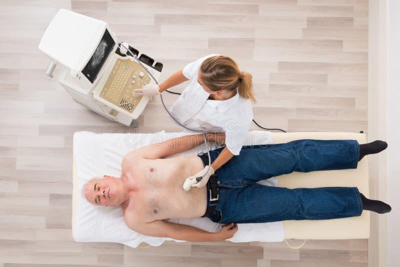 Docteur Using Ultrasound Scan sur l'abdomen du patient masculin supérieur photos stock