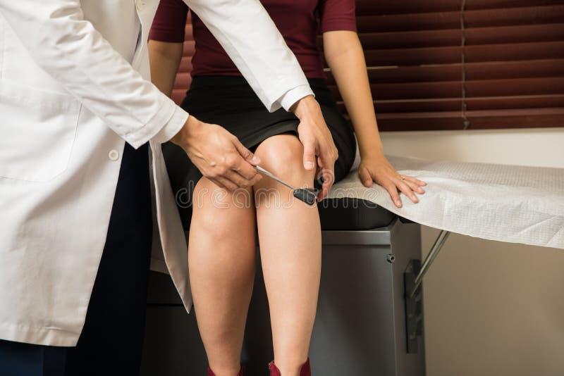 Docteur vérifiant des réflexes du ` un s de femme images libres de droits