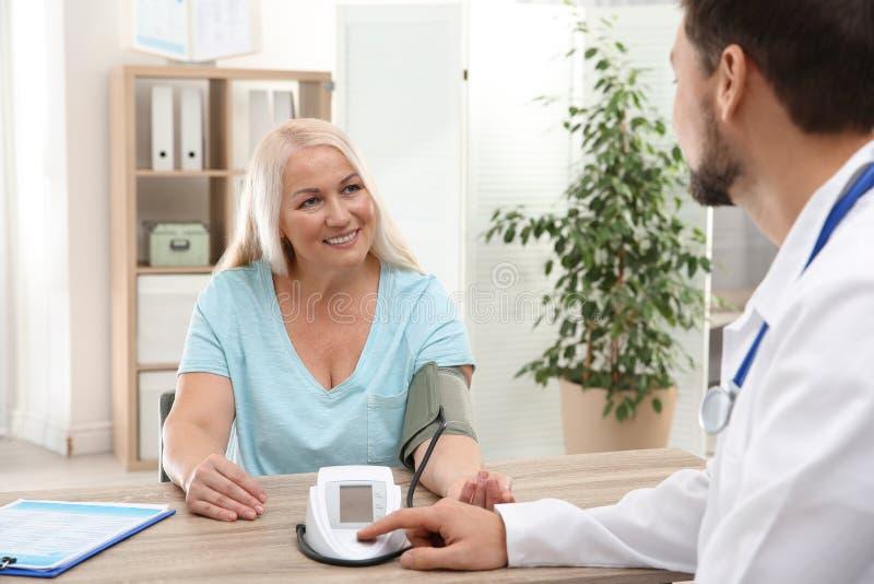 Docteur vérifiant l'impulsion de la femme mûre avec le dispositif médical photo libre de droits