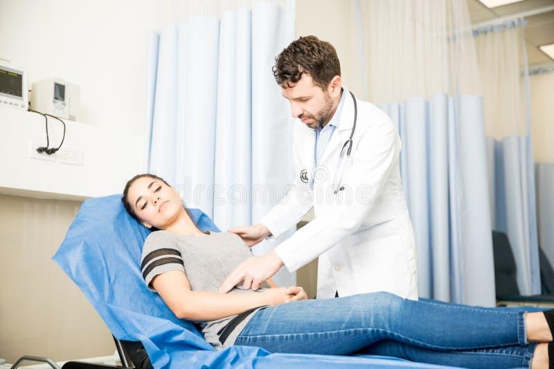 Docteur vérifiant la femme avec le mal d'estomac images libres de droits