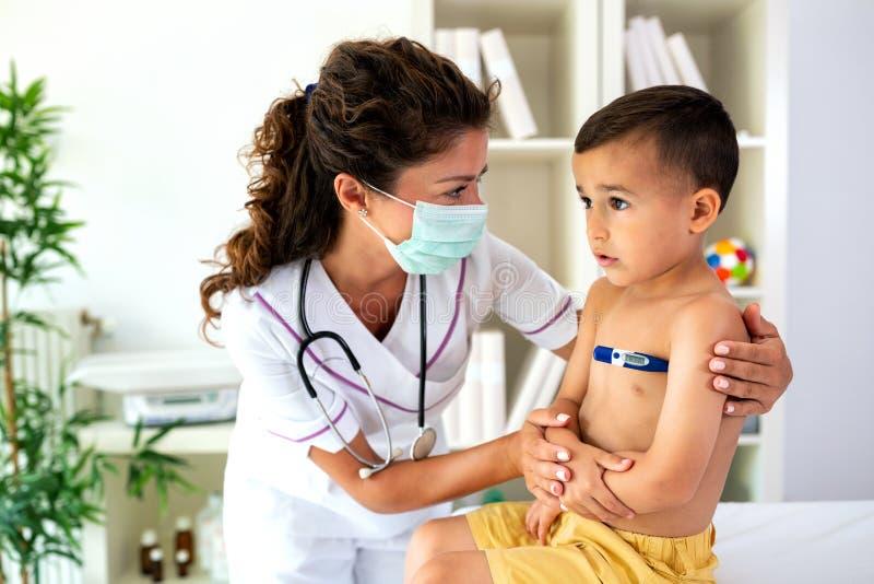 Docteur vérifiant la température corporelle du jeune garçon images libres de droits