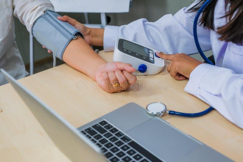 Docteur vérifiant la tension artérielle de sang artériel patiente de femme Santé C images stock