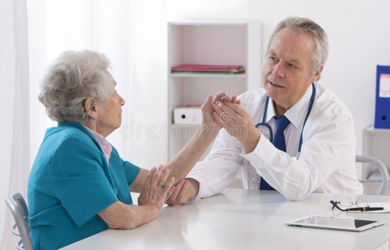 Docteur vérifiant le bras blessé du patient féminin photos libres de droits
