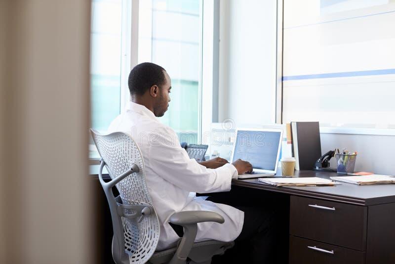 Docteur Wearing White Coat travaillant sur l'ordinateur portable dans le bureau photo stock