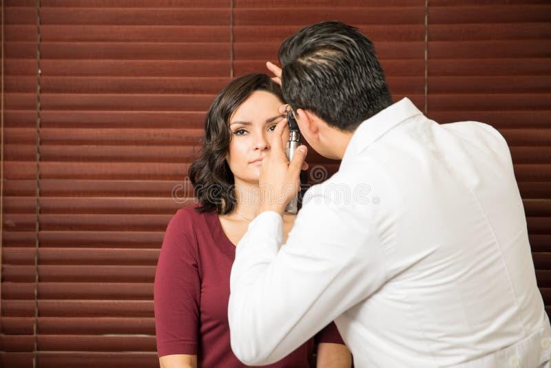 Docteur yeux de examen du ` un s de femme images stock