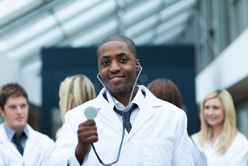 Doctor étnico con sus personas en el fondo imagenes de archivo
