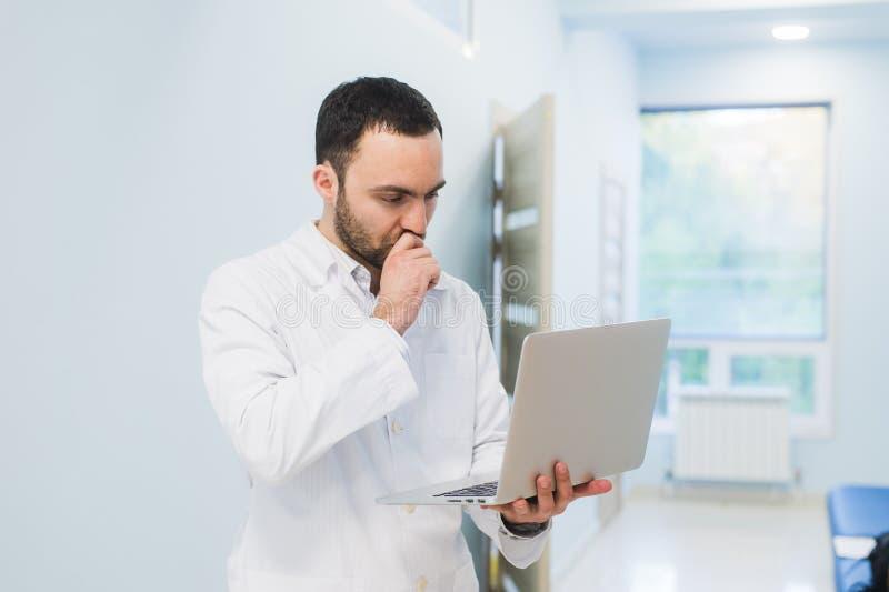 Doctor acertado importado que se coloca en su oficina y que usa el ordenador portátil para su trabajo imagen de archivo