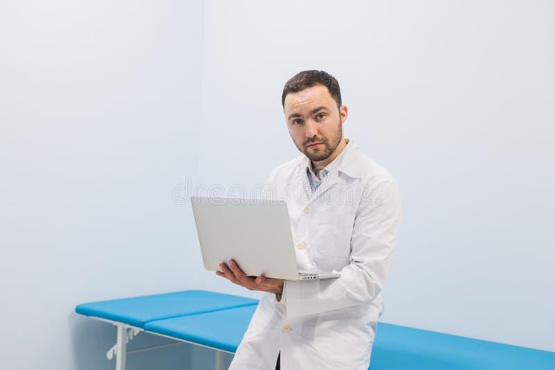 Doctor acertado importado que se coloca en su oficina y que usa el ordenador portátil para su trabajo fotos de archivo