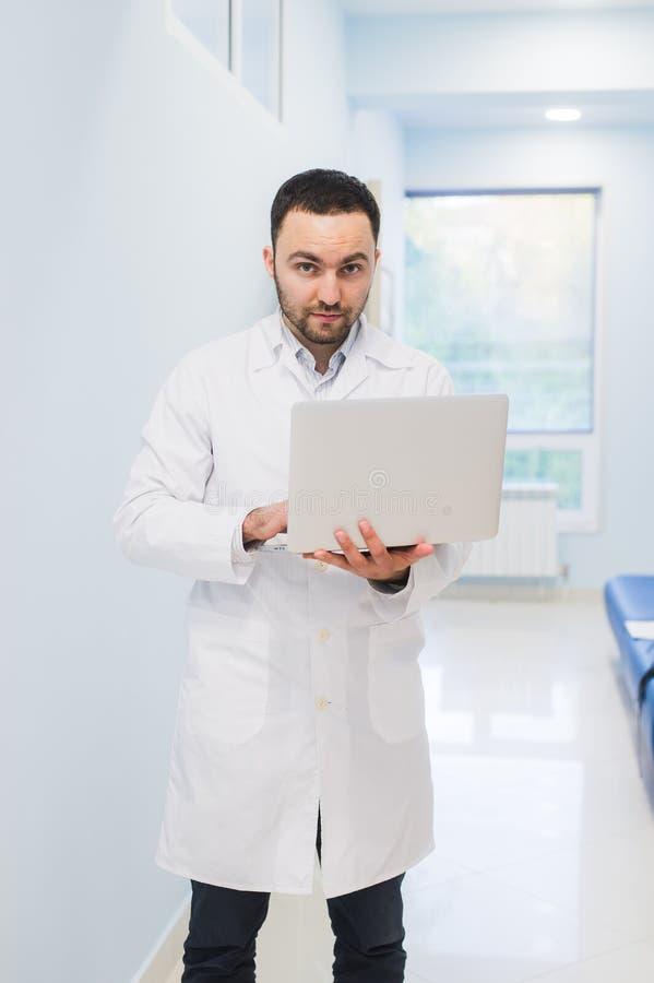 Doctor acertado importado que se coloca en su oficina y que usa el ordenador portátil para su trabajo imagenes de archivo