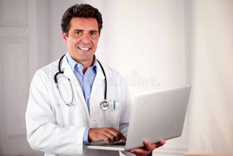 Doctor adulto encantador que usa su ordenador portátil foto de archivo