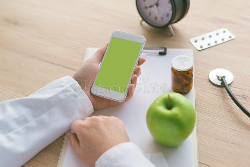 Doctor advising apple instead of pills and antibiotics stock photos