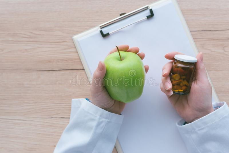 Doctor advising apple instead of pills and antibiotics stock photography