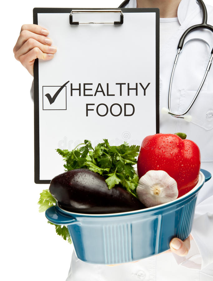 Doctor advising healthy food. Closeup of doctor's hands holding clipboard with marked checkbox Healthy food and brazier with fresh vegetables; healthy eating stock photography