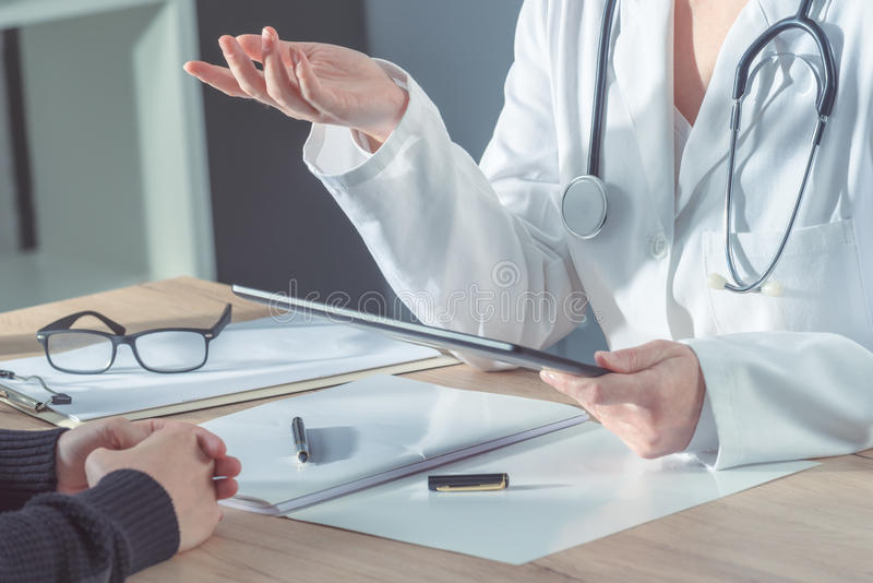 Doctor advising patient in hospital office stock photo