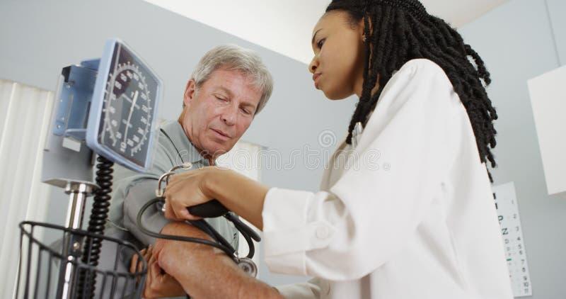 Doctor africano de la mujer que comprueba la presión arterial del paciente foto de archivo