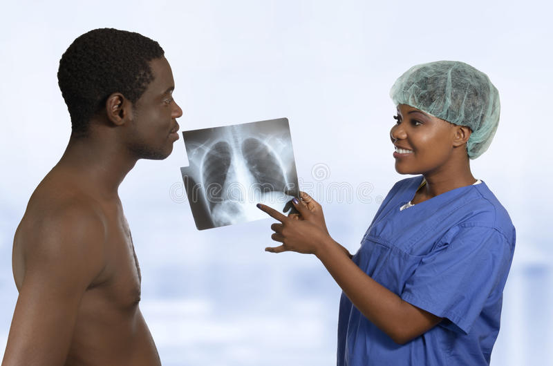 Doctor africano que explica imagen de la radiografía al paciente imagen de archivo libre de regalías