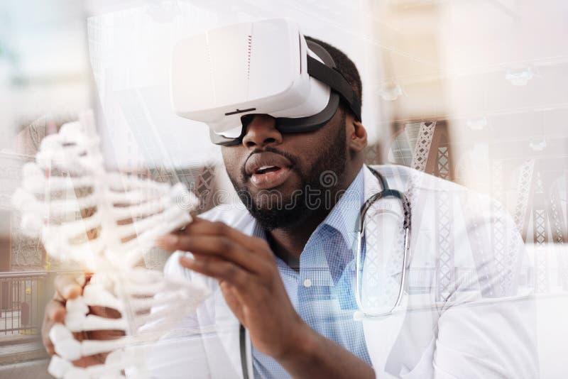 Doctor afroamericano concentrado con la maqueta del genoma fotos de archivo libres de regalías