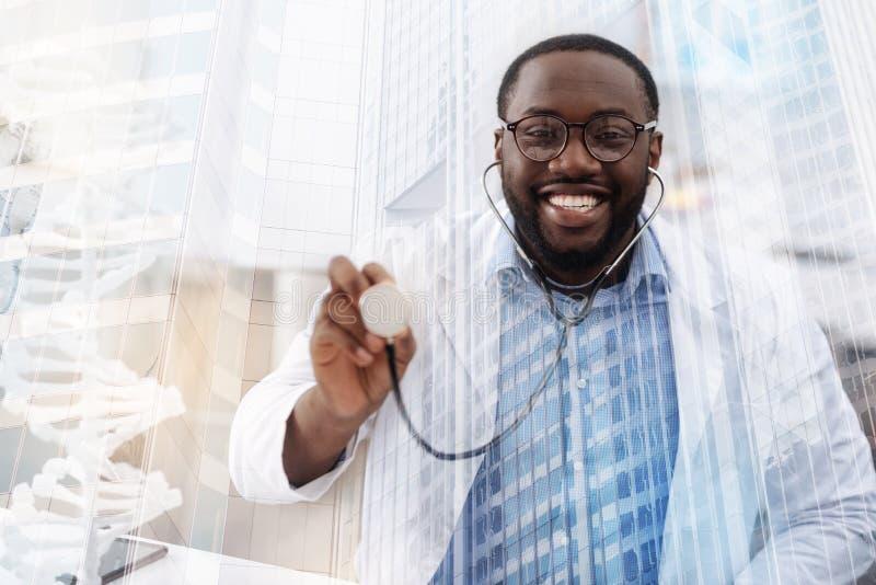 Doctor afroamericano divertido que usa los auriculares médicos fotos de archivo libres de regalías