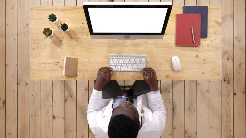 Doctor afroamericano joven en el trabajo Visualización blanca foto de archivo
