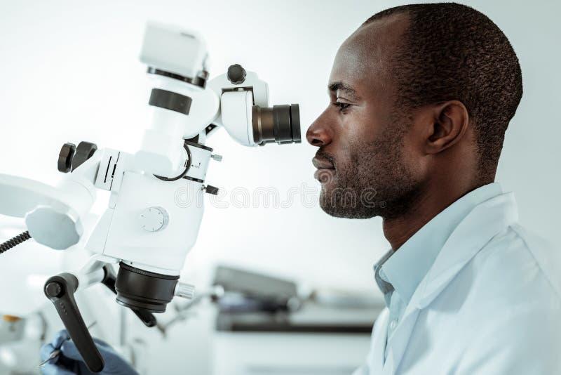 Doctor afroamericano que trabaja como dentista en hospital fotos de archivo