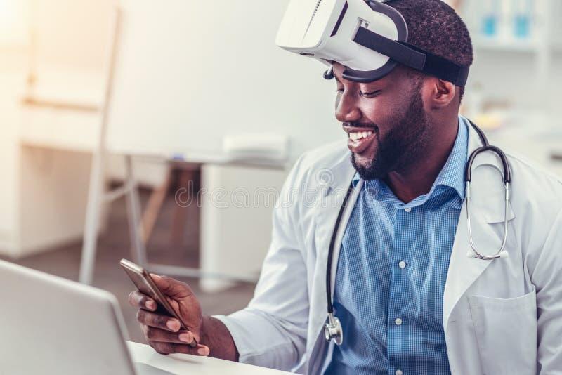 Doctor afroamericano relajado en vidrios de la realidad virtual usando smartphone fotos de archivo libres de regalías