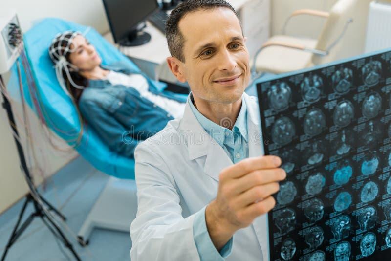 Doctor agradable que es satisfecho por resultados del CT de su paciente imagen de archivo libre de regalías