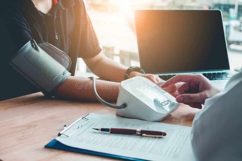 Doctor al paciente arterial de la mujer de la presión arterial de Measuring en la derecha fotografía de archivo