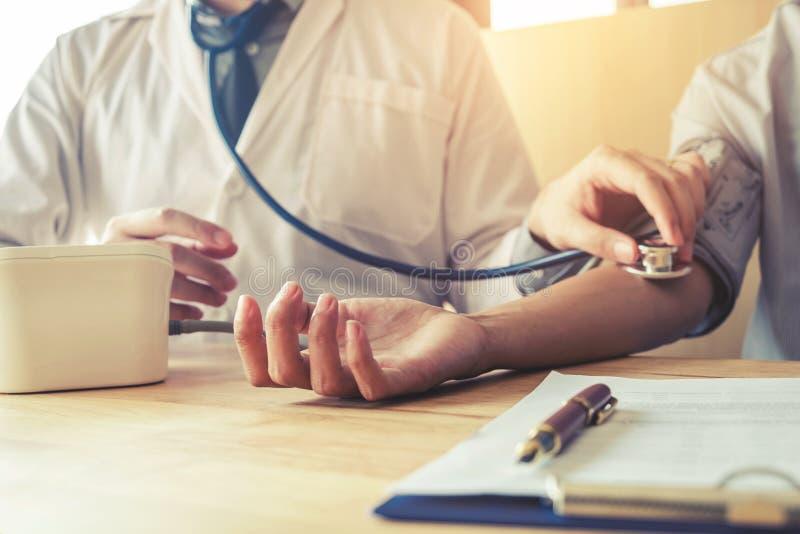 Doctor al paciente arterial de la mujer de la presión arterial de Measuring en el brazo él fotos de archivo