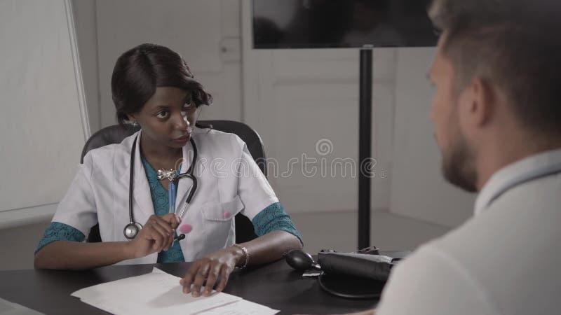 Doctor al paciente masculino de examen de In White Coat en la oficina, presión arterial, enfermera negra afroamericana en hospita foto de archivo