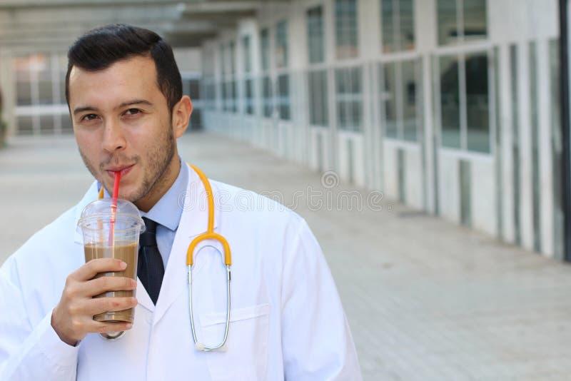 Doctor alegre que sorbe su latte imágenes de archivo libres de regalías