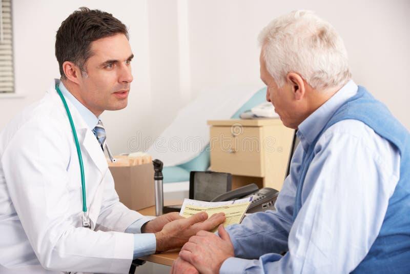Doctor americano que habla con el hombre en cirugía foto de archivo libre de regalías