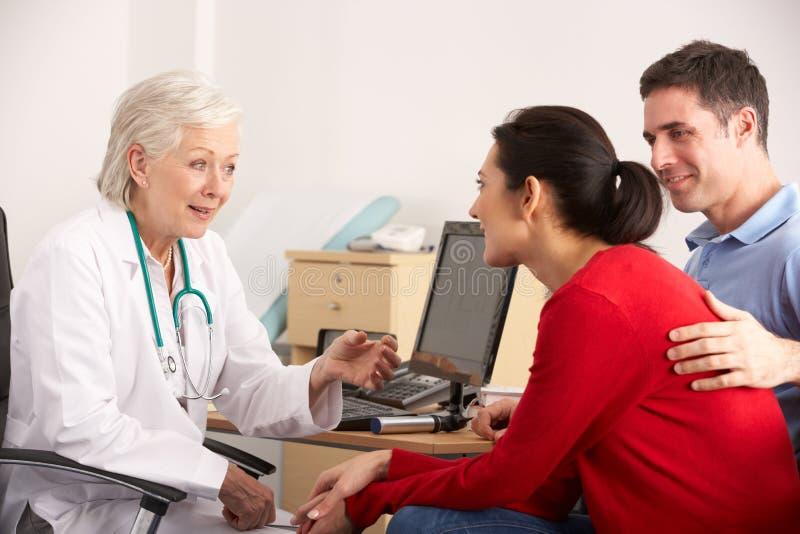 Doctor americano que habla con los pares felices en cirugía imágenes de archivo libres de regalías