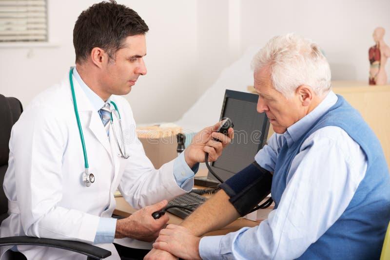 Doctor americano que toma la presión arterial del hombre mayor foto de archivo libre de regalías