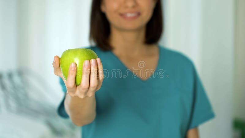 Doctor amistoso de la señora que sostiene el primer de la manzana, promoción sana de la nutrición, adietando foto de archivo libre de regalías