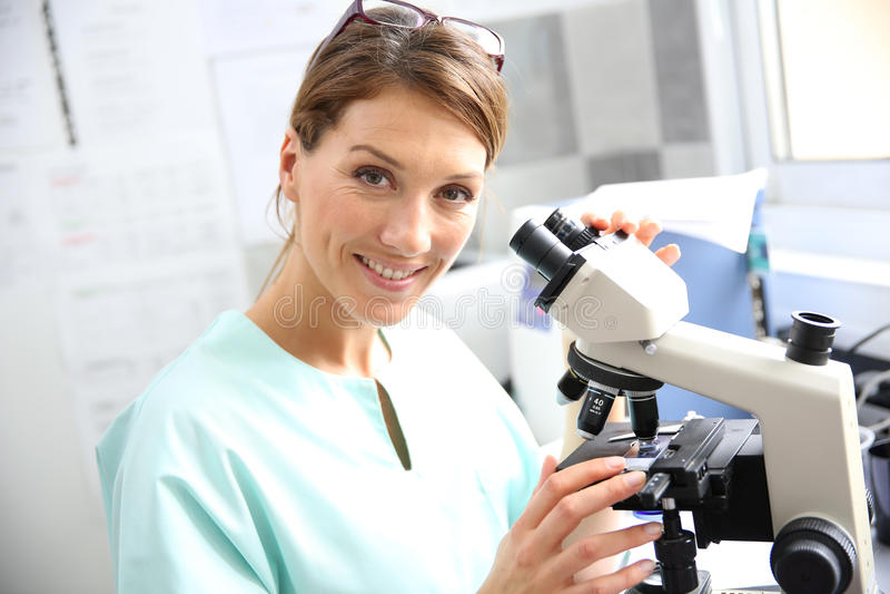 Doctor analysing samples through microscope stock photo