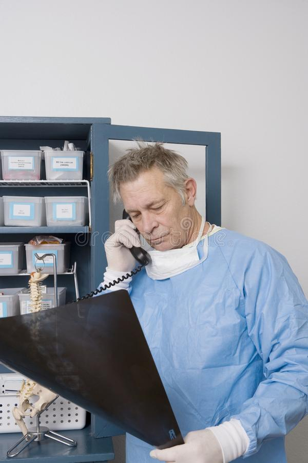 Doctor Analyzing X-Ray Report While Using Landline Phone. Senior male doctor using landline phone while analyzing x-ray report in clinic stock photo